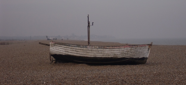 Old fishing boat on the shingle in the mist.